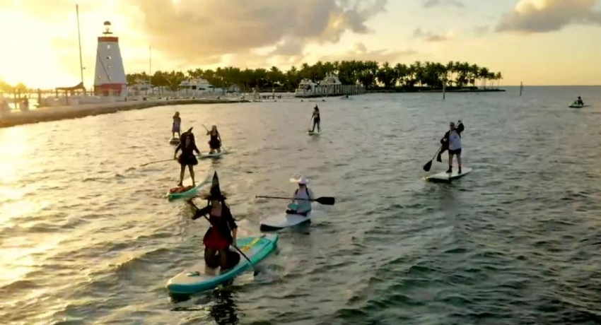 Witches celebrate October full moon by paddleboarding in the Florida Keys