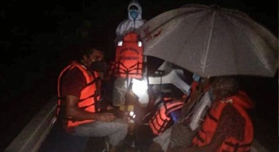 Navy relief teams rescue flood victims trapped in a tree in Galle
