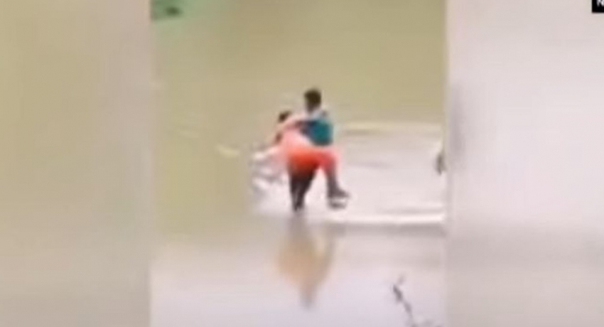 (VIDEO) Man carries pregnant wife across flood waters because ambulance couldn't get to them