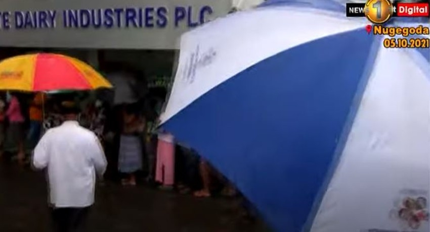 (VIDEO) Hundreds line up for hours despite inclement weather to buy Milk Powder